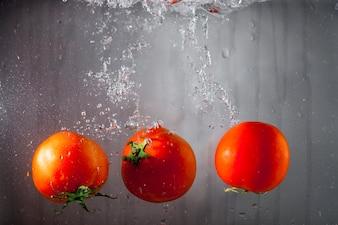 Three tomatoes falling in water