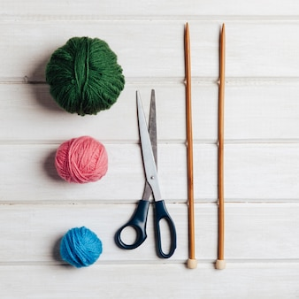 Three wool balls, scissors and needles