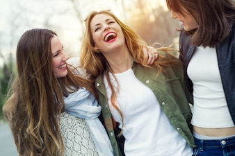 Three young women talking and laughing in the street.