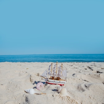 Tiny ship and seashells in composition