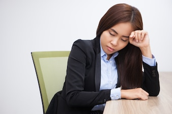 Tired Asian young businesswoman sleeping at table