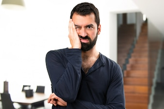 Tired handsome man with beard inside house