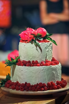 Tired wedding cake decorated with raspberries