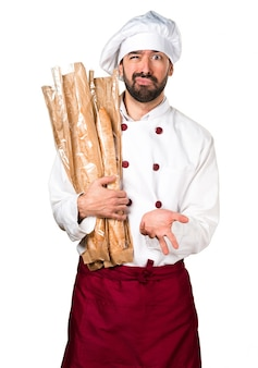 Tired young baker holding some bread