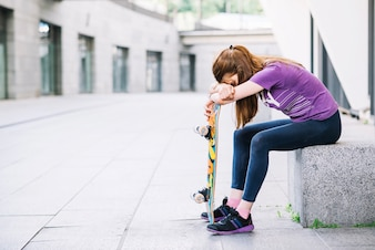 Tired young girl with skateboard sits on border