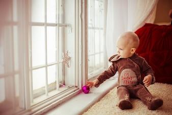 Toddler boy looking at window sitting