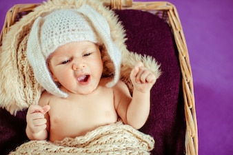 Toddler in hat lying in baby bassinet