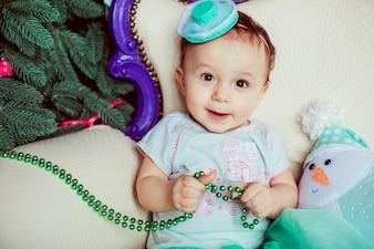 Toddler playing with garland sitting