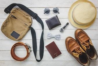 Вид сверху, чтобы путешествовать с концепцией мужской одежды. галстук-бабочка, кошелек на деревянный background.watch, солнцезащитные очки, сумка, шляпа, пояс и обувь на деревянном столе.