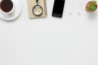 トップビューアクセサリービジネスオフィスdesk.mobile電話、コーヒー、ノート、コピースペースと白のオフィスデスクでイヤホン。