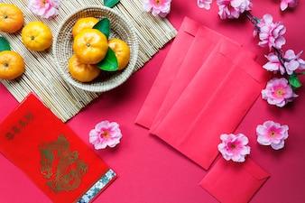 トップビューのアクセサリー中国の新年の祭りの装飾。蘭、葉、木のバスケット、赤いパケット、赤い背景に梅の花。栄養的な言語は豊かで幸せを意味します。