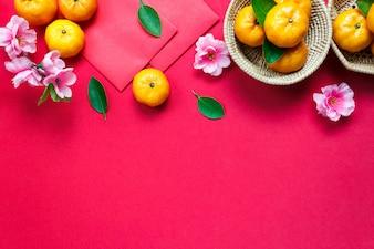 トップビューのアクセサリー赤い背景に中国の新年の祭り装飾。蘭、木のバスケット、赤いパケット、梅の花。