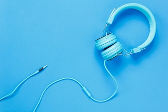 Top view blue headphones on blue background with copy space.