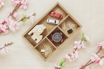 Концепция рабочего стола с наивысшим видом. Деревянный дом также автомобиль и часы на деревянной полке. Красивый розовый цветок на фоне дерева с копией пространства.