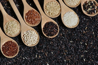Top view different rice on wooden scoop with black riceberry background, Various rice organic on wooden spoon collection