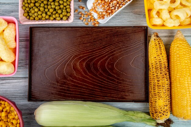 Top view of empty tray with green peas corn seeds corn pop cereals and corn cobs on wooden surface