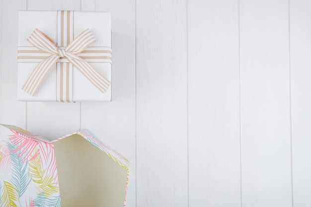 Top view of gift boxes on white wooden background with copy space