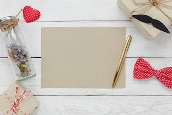 Вид сверху Счастливый день отца. Цветная бумага для свободного текста на деревенском деревянном фоне. Аксессуары с красным сердцем, подарок, усы, винтажный галстук-бабочка, сушеный цветок в бутылке и подарок.