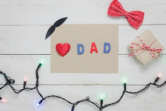 Top view Happy Father day.Red heart and word  DAD  on rustic wooden background.accessories with paper,lights,gift,mustache,vintage bow tie present and tree.