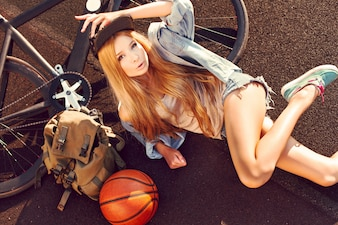 Top view of blonde woman lying next to her bicycle and backpack