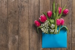 Top view of blue envelope with flowers on wooden table