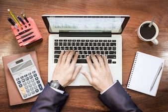木製の机の上でラップトップやタブレットPCで働くビジネスマンの手の上の眺め。