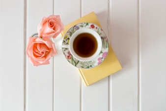 Top view of cup of tea with two decorative flowers
