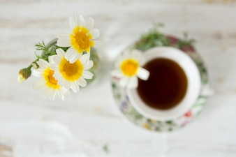 Top view of daisies with blurred cup of tea