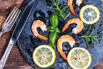 Top view of delicious shrimps with lemon slices
