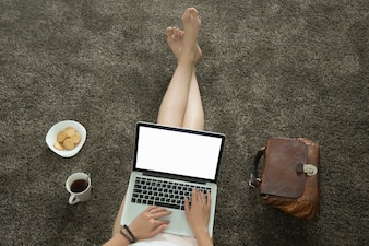 Top view of female lying on carpet with a laptop