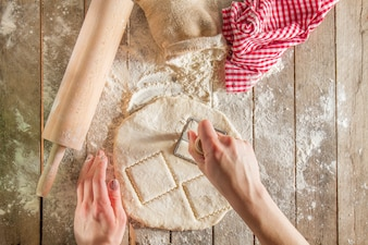 Top view of hands cutting the dough