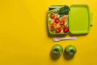 Top view of lunch box with salad and two apples