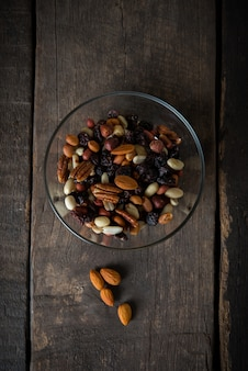 Top view of Mix nuts in bowl on wooden background.