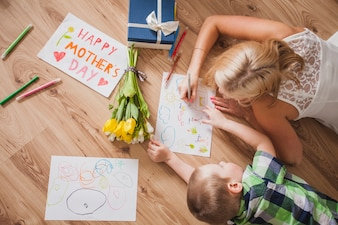 Top view of mother and son drawing next to a mother's day poster