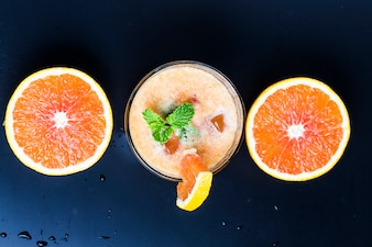 Top view of orange juice with mint and oranges