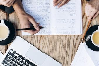 コピーブック、本、ラップトップで勉強している人のトップビュー。テーブル上のコーヒーカップ