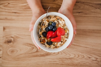 Top view of person holding muesli bowl