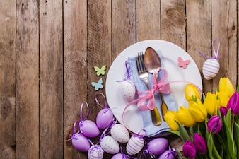 Top view of table with easter eggs and decorative flowers