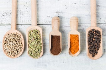 Top view of wooden spoons with spices and legumes