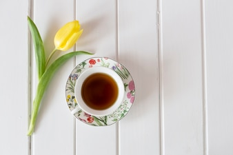 Top view of yellow tulip with cup of tea