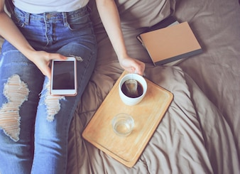 Top view of young woman in casual clothes using smartphone on bed with tea and notebook, lifestyle concept