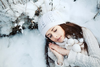 Top view of young woman sleeping on the snowy ground