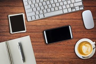 Верхний офисный стол с блокнотом, компьютер и чашка кофе, компьютерная мышь и рамка. Вид сверху с копией.