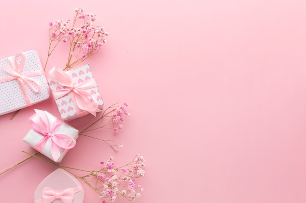 Top view of pink gifts with flowers and copy space