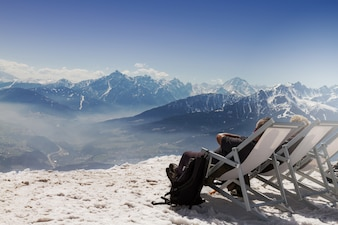 Tourist chilling seating in chaise-longue sunbed on mountain background, snow. Horizontal. Copy Space. Tourism winter concept.