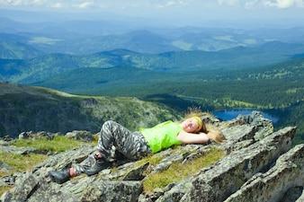 Tourist resting at mountain peak