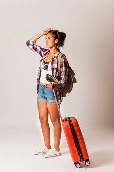 旅行の女性、スーツケースを見回す