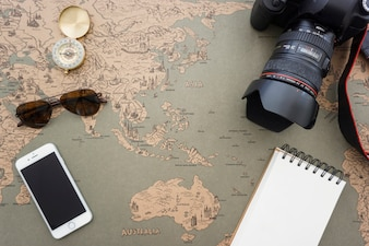 Travel items on vintage world map
