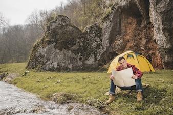 キャンプで地図をチェックしている旅行者