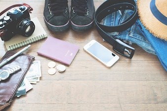 Traveler's accessories, Essential vacation items of young man with passport, camera, mobile device and purse on wood background with copy space